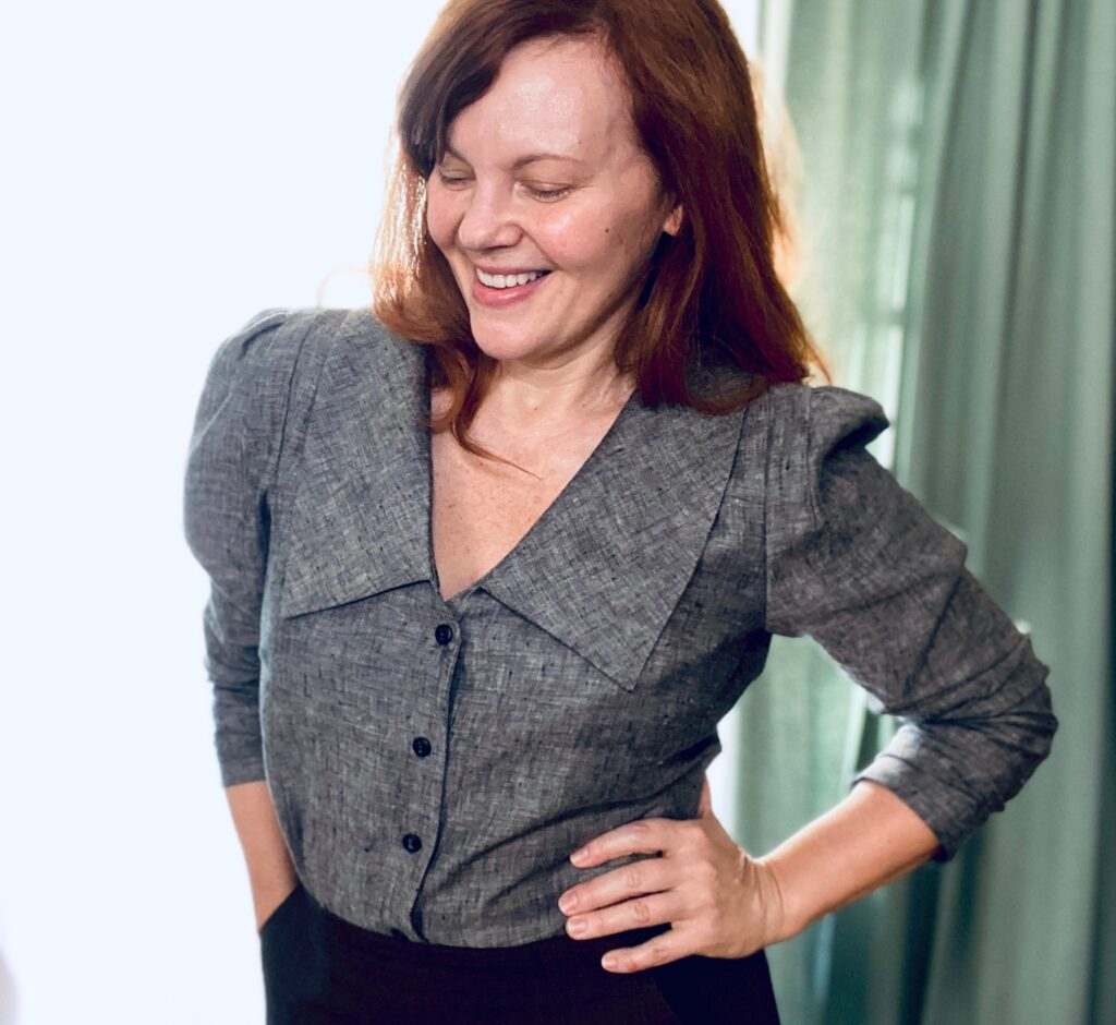 A mid-50s white woman with red hair stands in front of a mint green curtain. She is smiling with one hand on her hip, the other in her pocket. She wears a grey blouse with large collar and puffy sleeves.
