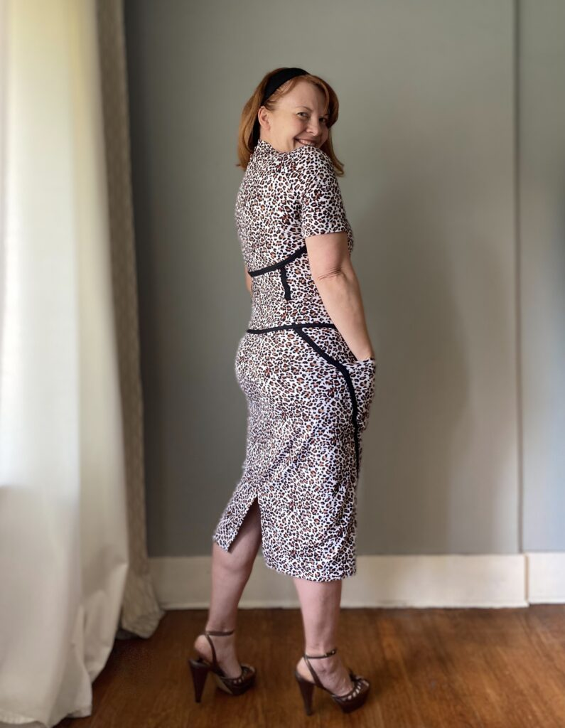 A mid-50s white woman with red hair stands in front of a grey wall turned three-quarters to the wall looking back over her shoulder. She is smiling and wears a handmade animal print top and skirt with black seam detailing.