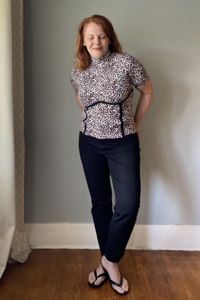 A mid-50s white woman with red hair stands in front of a grey wall. She wears a handmade animal print top and skirt with black seam detailing and slim black pants.
