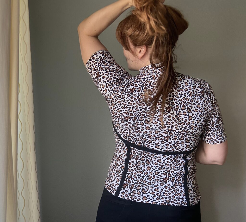 A mid-50s white woman with red hair faces a grey wall looking to the left. She holds her hair up with her left hand and wears a handmade animal print top with black seam detailing.