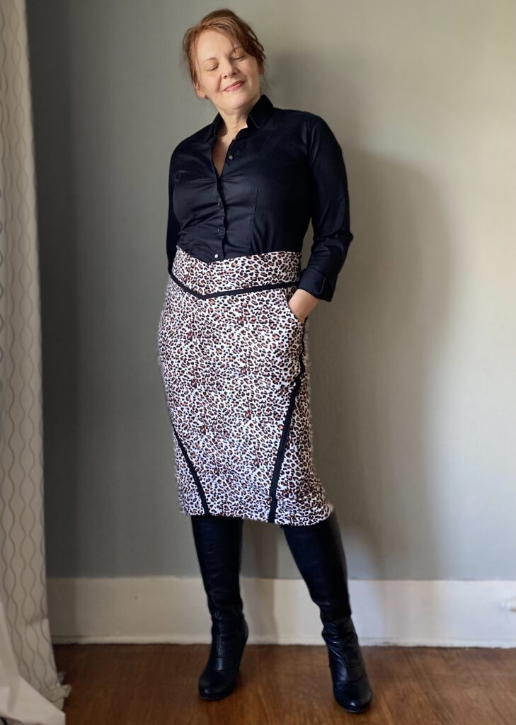 A mid-50s white woman with red hair stands in front of a grey wall . She wears a handmade black button down  shirt, and animal print skirt with black seam detailing.