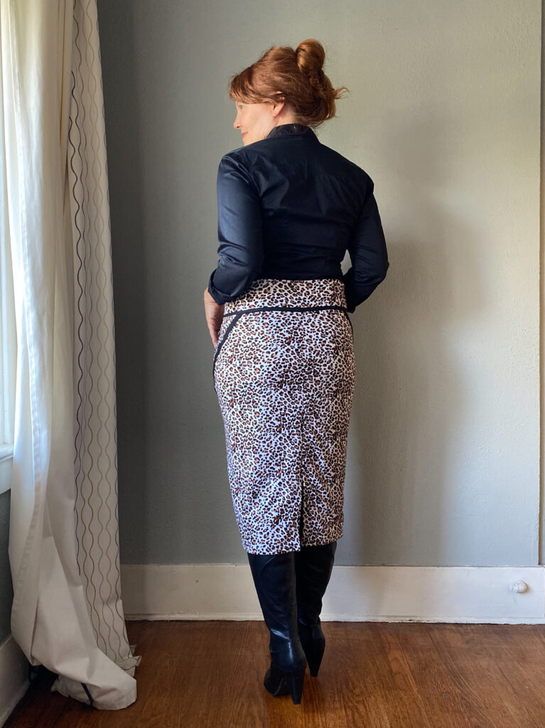 A mid-50s white woman with red hair stands facing a grey wall looking to the left . She wears a handmade black button down  shirt, and animal print skirt with black seam detailing.