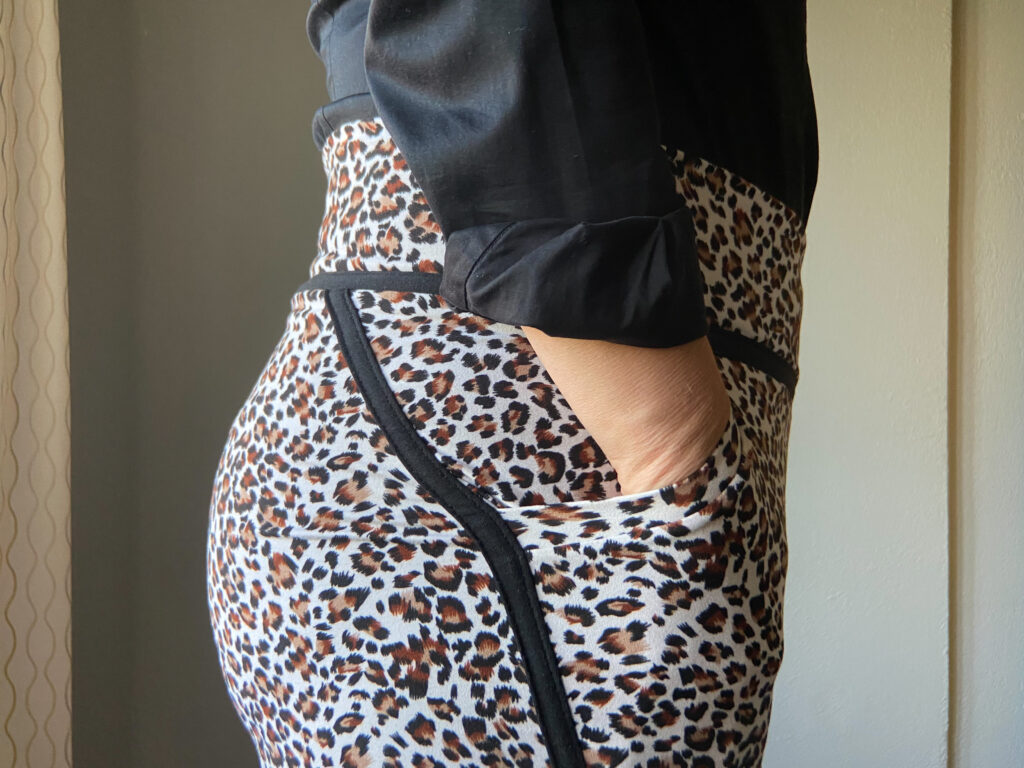 A close-up side view of a fitted animal print skirt with black seam detail at the waist and side seam.