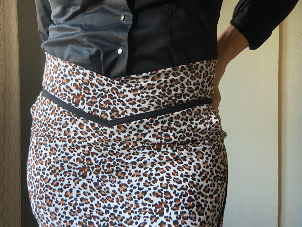 A close-up front view of a fitted animal print skirt with black seam detail at the waist.