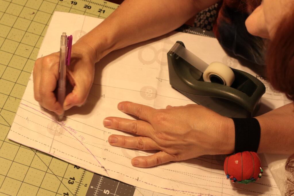 A white woman draws a pocket pattern piece on a gridded mat