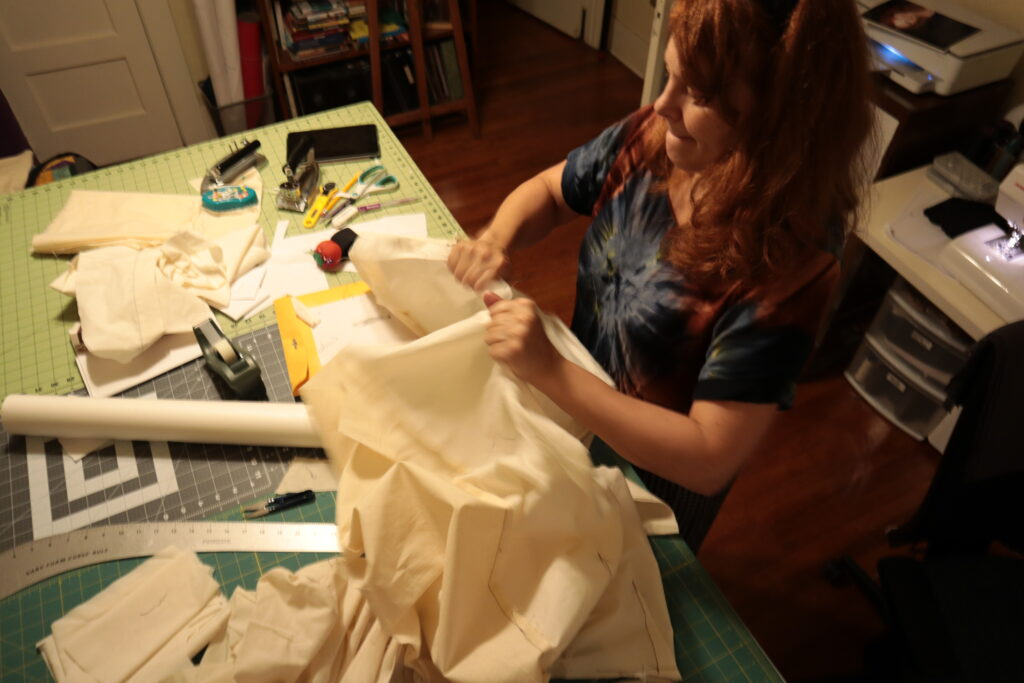 A white woman with red hair tears apart a toile in her sewing room