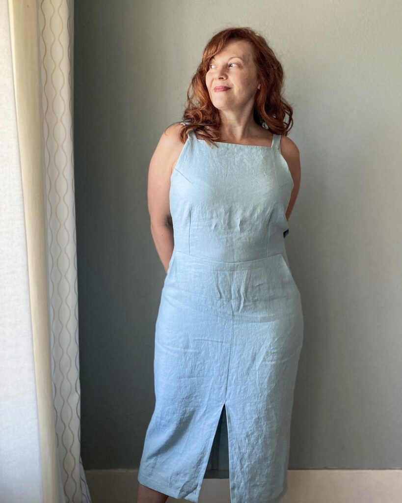 A mid-50s white woman with red hair stands facing a grey wall wearing a handmade light blue sundress.