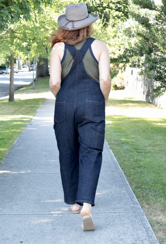 A woman with long red hair wearing denim overalls and a straw hat walks away from camera.