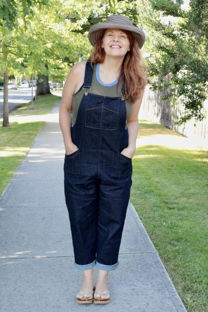 A woman with long red hair stands wearing denim overalls and a straw hat with her hands in her pockets.