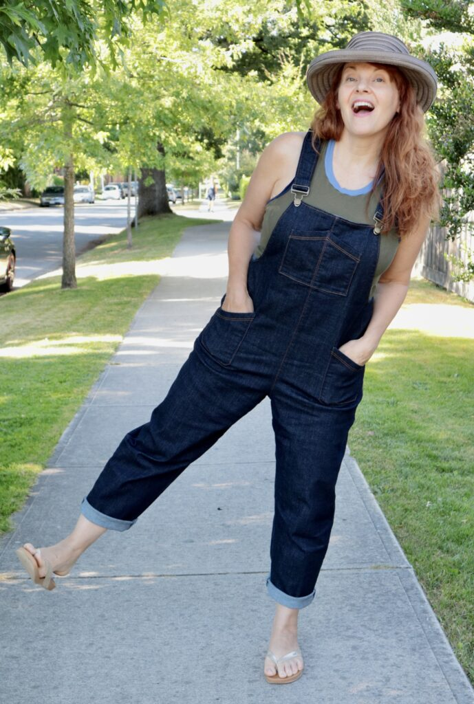 A woman with long red hair stands on one foot wearing denim overalls and a straw hat.