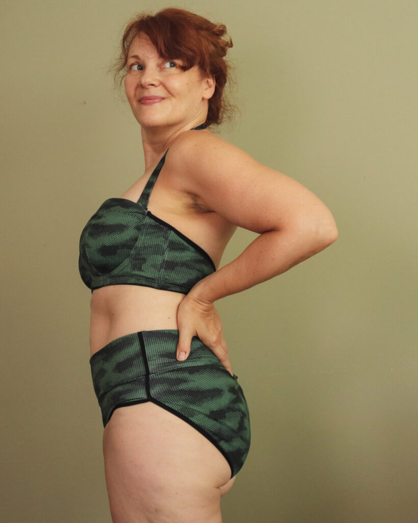 A white woman with red hair stands sideways wearing a two-piece camouflage swim suit
