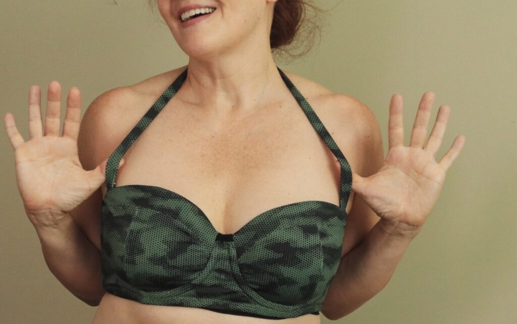 A white woman smiles wearing a camouflage print swim top with thumbs hooked on the halter strap
