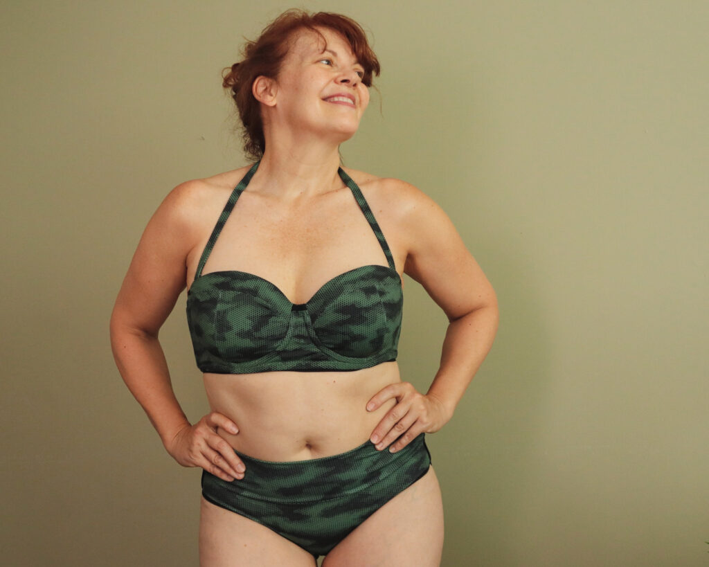 A white woman with red hair smiles with hands on hips wearing a two-piece camouflage swim suit