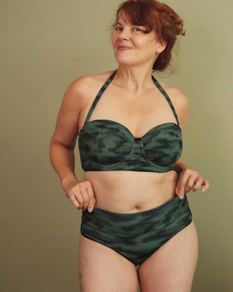 A white woman with red hair wears a two-piece camouflage swim suit