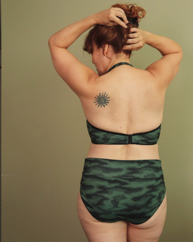 A white woman with red hair faces away from camera with her hands in her hair wearing a two-piece camouflage swim suit