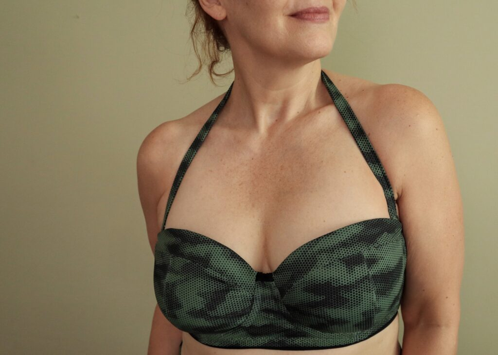 A white woman wears a halter style camouflage print swim suit top