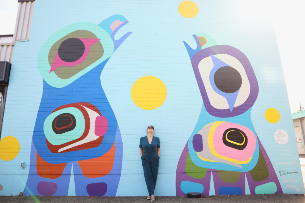 A white woman with red hair stands in front of a colourful mural by First Nations artist Steve Smith - Dla'kwagila . She wears a teal jumpsuit and sunglasses.