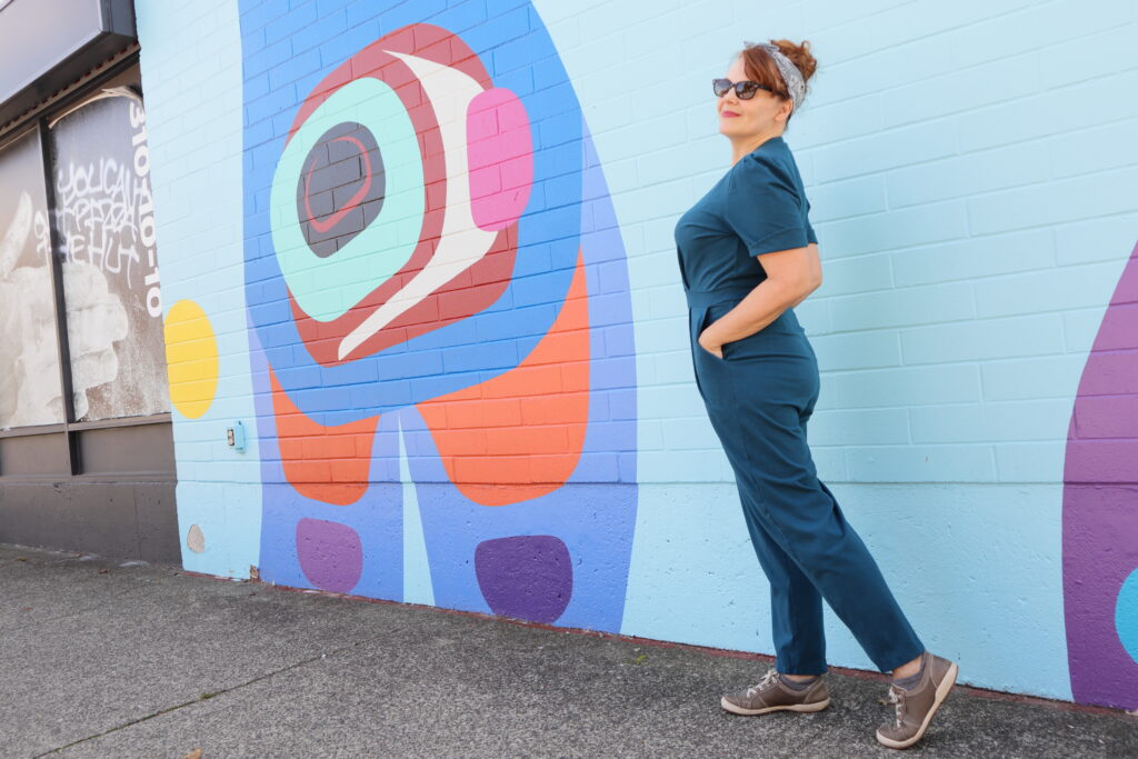 A white woman with red hair stands in front of a colourful mural wearing a teal jumpsuit and sunglasses.