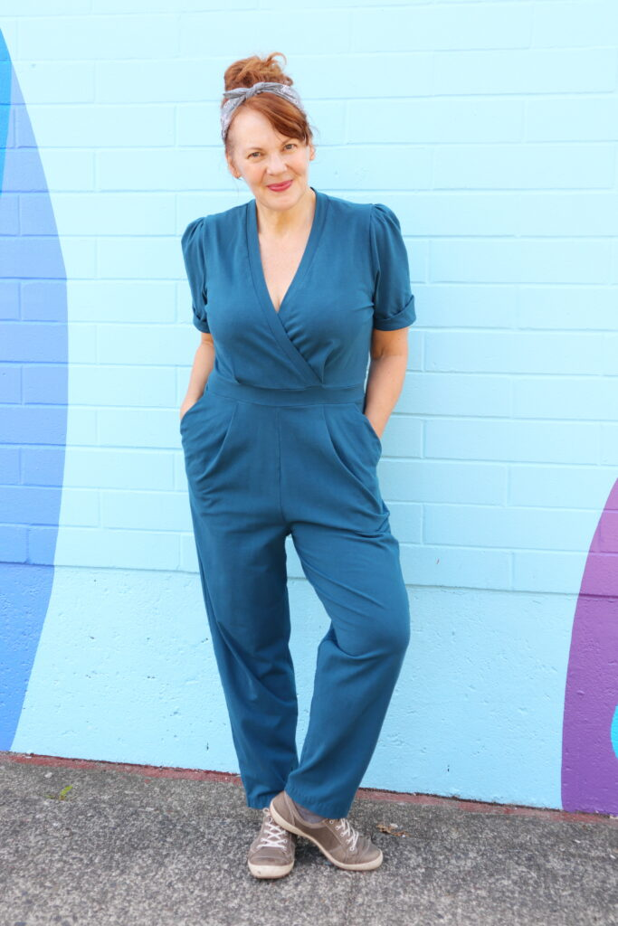 A white woman with red hair stands in front of a blue wall wearing a teal jumpsuit.