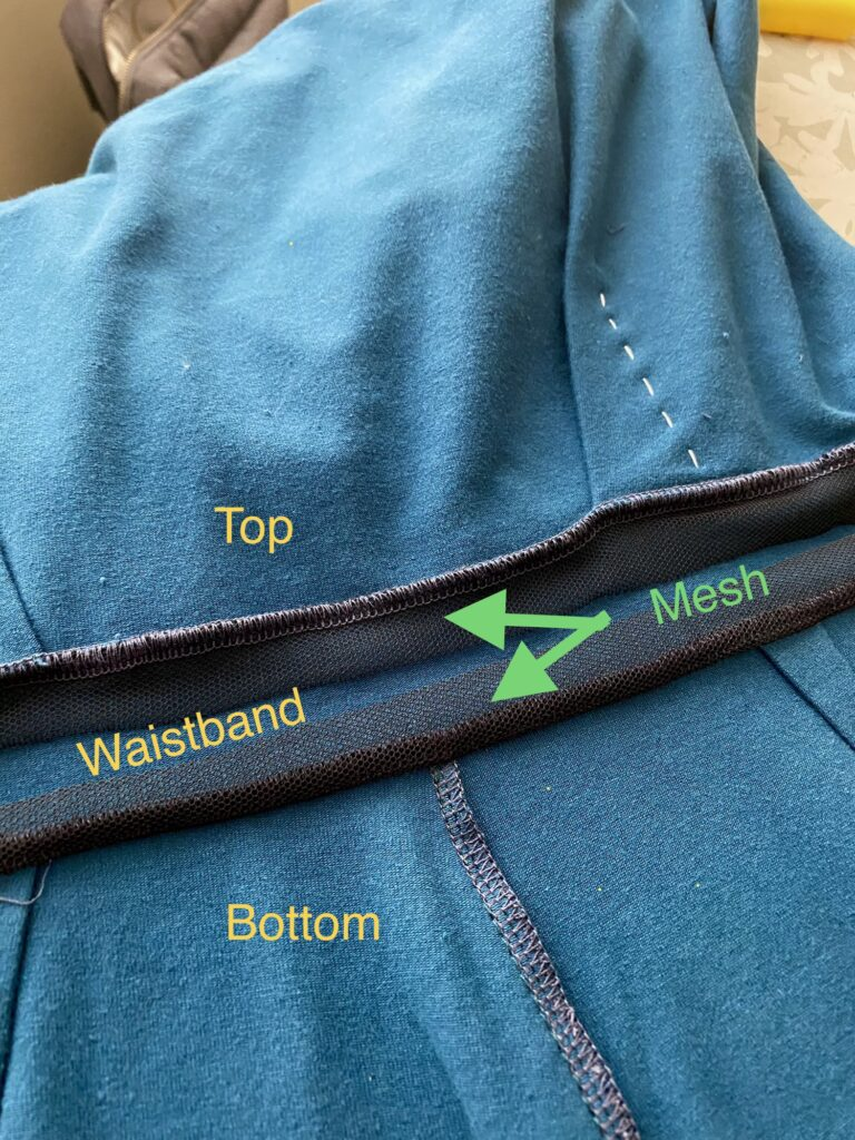 Detail shot of a waistband sewn into a teal top and bottom with mesh sewn into the seams.