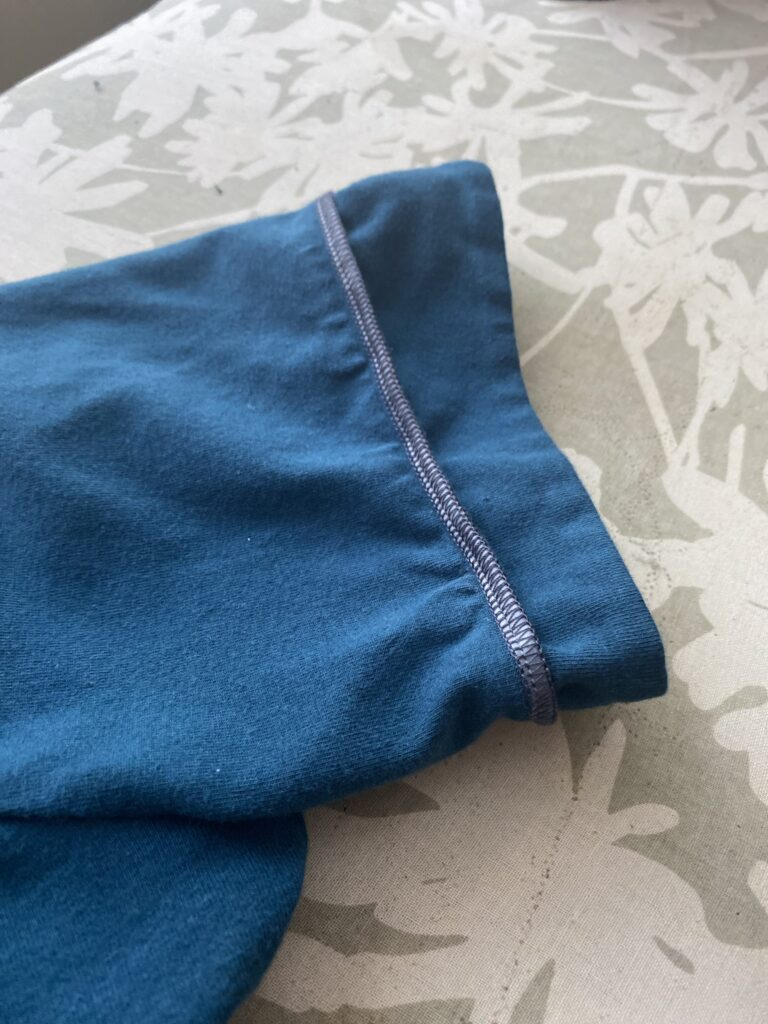 Detail shot of clear elastic sewn into teal sleeve cuff.