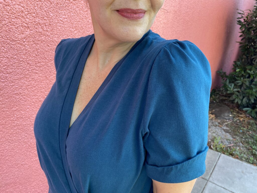 Detail of white woman standing next to a salmon pink wall wearing a teal jumpsuit with puffy short sleeves.