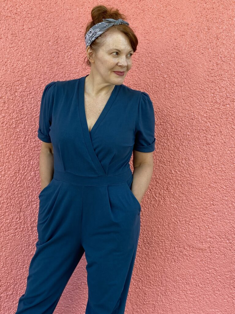 A white woman with red hair stands in front of a salmon pink wall wearing a teal jumpsuit.