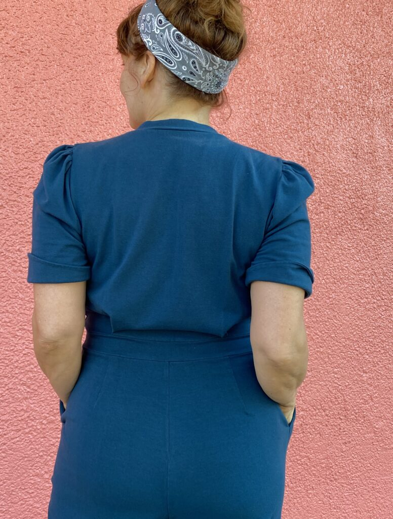 A white woman with red hair stands with back to camera wearing a teal jumpsuit against a salmon pink wall.
