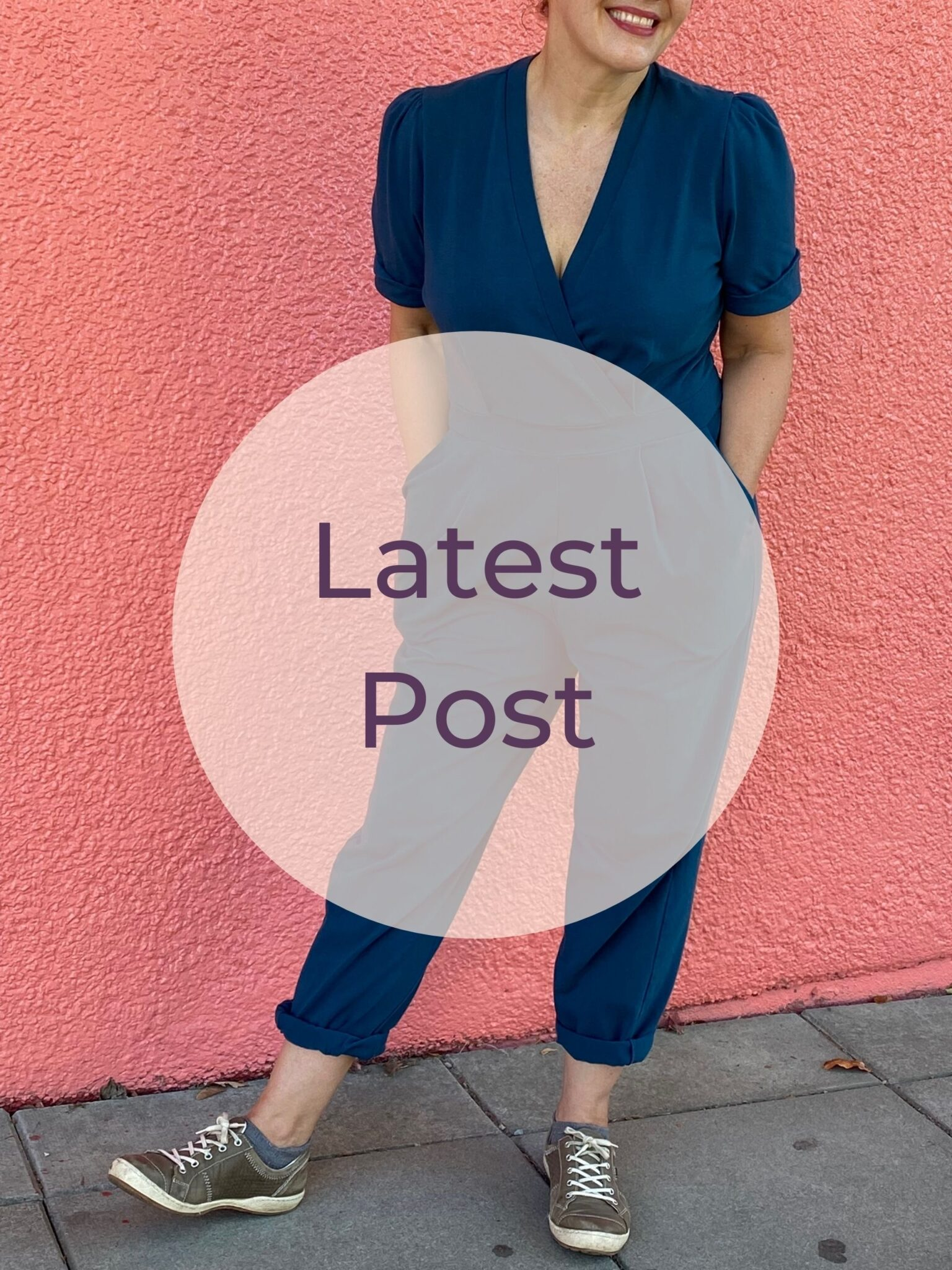 A white woman stands in front of a salmon pink wall wearing a teal jumpsuit. A pink circle with text reading latest post is superimposed.